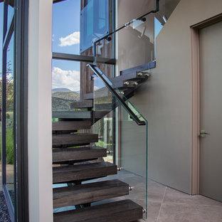 Foto de escalera curva, contemporánea, grande, sin contrahuella, con escalones de madera y barandilla de vidrio