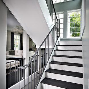 Foto de escalera en U, moderna, grande, con escalones de madera, contrahuellas de madera pintada y barandilla de metal