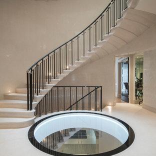 Foto de escalera curva, moderna, grande, con escalones de piedra caliza, contrahuellas de piedra caliza y barandilla de metal