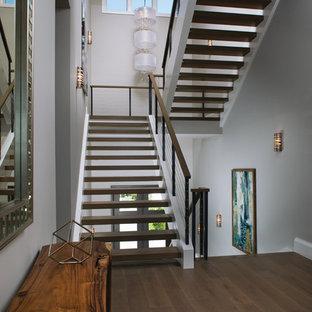 Modelo de escalera suspendida, actual, grande, sin contrahuella, con escalones de madera y barandilla de cable
