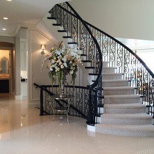 Imagen de escalera curva, clásica, grande, con escalones de madera pintada y contrahuellas de madera pintada