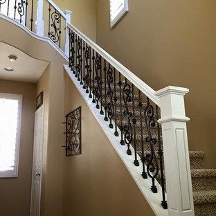 Ejemplo de escalera en L, clásica, grande, con escalones enmoquetados, contrahuellas enmoquetadas y barandilla de varios materiales