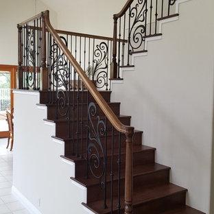 Exempel på en mellanstor klassisk u-trappa i trä, med sättsteg i trä och räcke i flera material