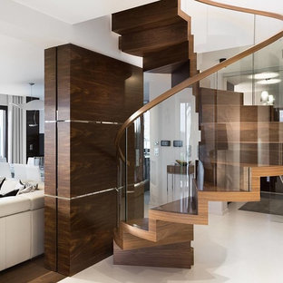 Trendy wooden spiral glass railing staircase photo in New York with wooden risers