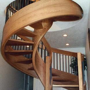 Foto di una grande scala a chiocciola chic con pedata in legno e nessuna alzata