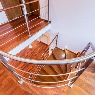 Ejemplo de escalera curva, moderna, grande, con escalones de madera y contrahuellas de metal