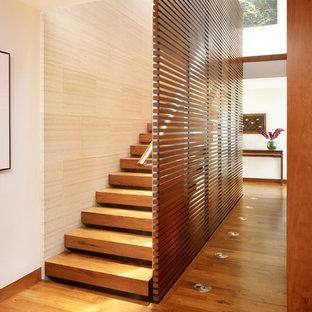 Imagen de escalera recta, de estilo zen, grande, sin contrahuella, con escalones de madera y barandilla de madera