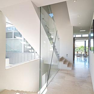 """Immagine di una scala a """"L"""" contemporanea di medie dimensioni con pedata in pietra calcarea, alzata in pietra calcarea e parapetto in vetro"""