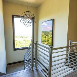 Diseño de escalera en U, moderna, grande, con escalones de madera, contrahuellas de madera y barandilla de metal