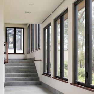 Стильный дизайн: большая угловая лестница в стиле модернизм с ступенями из сланца, подступенками из сланца и деревянными перилами - последний тренд