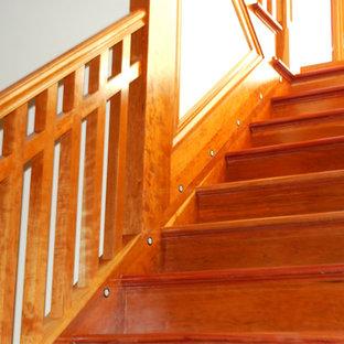 Ejemplo de escalera curva, de estilo americano, extra grande, con escalones de madera y contrahuellas de madera