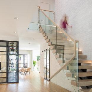 Imagen de escalera en L, minimalista, de tamaño medio, sin contrahuella, con escalones de madera y barandilla de vidrio