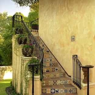 他の地域の中サイズのタイルのエクレクティックスタイルのおしゃれなサーキュラー階段 (タイルの蹴込み板、金属の手すり) の写真