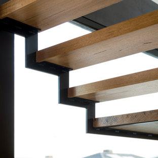 Esempio di una scala sospesa design di medie dimensioni con pedata in legno, nessuna alzata, parapetto in metallo e pareti in legno