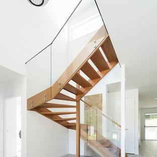 Foto de escalera en U, exótica, pequeña, con escalones de madera y barandilla de vidrio