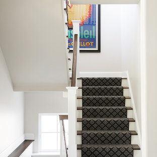 Staircase - transitional carpeted u-shaped wood railing staircase idea in Minneapolis with carpeted risers
