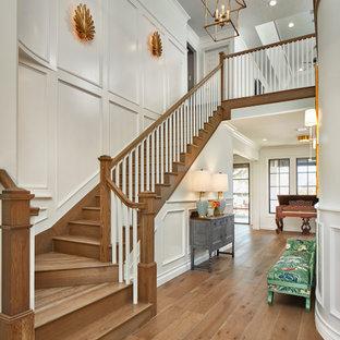 Foto de escalera en L y boiserie, clásica, grande, con escalones de madera, contrahuellas de madera, barandilla de madera y boiserie