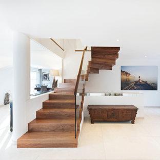 """Foto di una scala a """"U"""" mediterranea con pedata in legno, alzata in legno e parapetto in vetro"""
