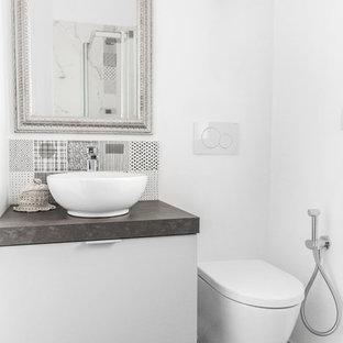 Foto di una stanza da bagno minimal con ante lisce, ante bianche, piastrelle nere, pareti bianche, lavabo a bacinella, pavimento grigio e top grigio
