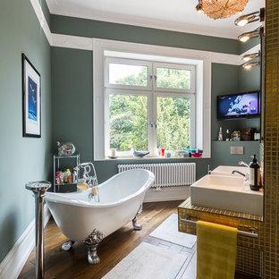 Esempio di una stanza da bagno tradizionale di medie dimensioni con lavabo a bacinella, vasca con piedi a zampa di leone, pareti verdi, parquet scuro, piastrelle gialle, piastrelle a mosaico e top piastrellato