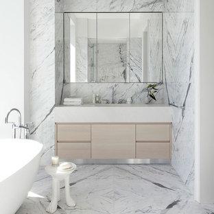Idee per una stanza da bagno padronale design con ante lisce, ante in legno chiaro, vasca freestanding, piastrelle bianche, piastrelle in pietra, pareti bianche e pavimento in marmo