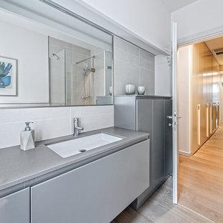 Ispirazione per una stanza da bagno contemporanea di medie dimensioni con ante lisce, ante grigie, piastrelle grigie, pareti bianche, parquet chiaro, lavabo sottopiano e pavimento beige