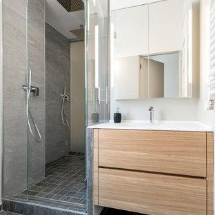 Idee per una stanza da bagno con doccia contemporanea di medie dimensioni con ante lisce, ante in legno chiaro, doccia doppia, piastrelle grigie, piastrelle in gres porcellanato, pavimento in gres porcellanato, pareti grigie, lavabo sottopiano, top in superficie solida e porta doccia a battente
