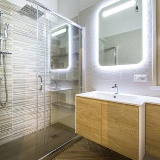 Immagine di una stanza da bagno con doccia minimal con ante lisce, doccia a filo pavimento, porta doccia scorrevole, top bianco, ante in legno chiaro, piastrelle multicolore, piastrelle a listelli, pareti bianche e lavabo integrato