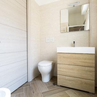 Ispirazione per una piccola stanza da bagno minimal con consolle stile comò, ante in legno chiaro, WC sospeso, piastrelle beige, pareti beige e pavimento beige