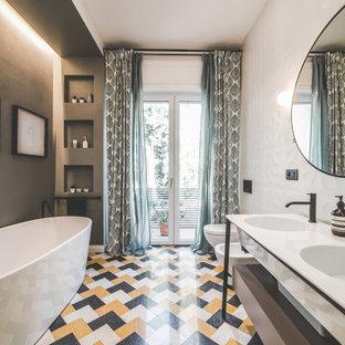 Esempio di una stanza da bagno contemporanea con ante lisce, ante grigie, vasca freestanding, pareti grigie, lavabo integrato, pavimento multicolore, top bianco e due lavabi