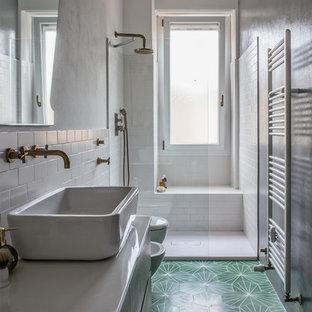 Mittelgroßes Shabby-Style Duschbad mit dunklen Holzschränken, offener Dusche, Wandtoilette, weißen Fliesen, Keramikfliesen, grauer Wandfarbe, Zementfliesen, Aufsatzwaschbecken, Mineralwerkstoff-Waschtisch, grünem Boden, offener Dusche und weißer Waschtischplatte in Mailand