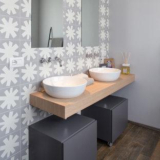 Imagen de cuarto de baño contemporáneo con armarios con paneles lisos, puertas de armario grises, baldosas y/o azulejos blancos, baldosas y/o azulejos grises, baldosas y/o azulejos de cerámica, paredes grises, suelo de madera oscura, lavabo sobreencimera, encimera de madera y encimeras beige