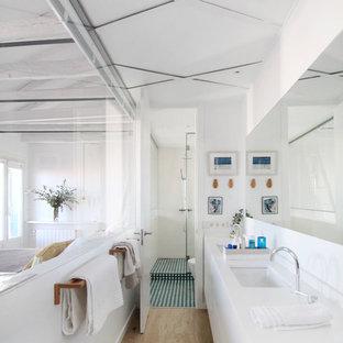 Modelo de cuarto de baño con ducha, contemporáneo, grande, con armarios con paneles lisos, ducha a ras de suelo, baldosas y/o azulejos azules, baldosas y/o azulejos de porcelana, lavabo encastrado, encimera de cuarzo compacto, encimeras blancas, puertas de armario blancas, paredes blancas, suelo de madera clara y suelo beige