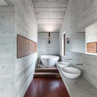 Modelo de cuarto de baño principal, moderno, grande, con puertas de armario de madera oscura, suelo de cemento, lavabo sobreencimera, encimera de cemento, suelo rojo, bañera exenta, combinación de ducha y bañera, paredes grises y ducha abierta