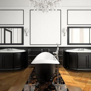 Foto di un'ampia stanza da bagno padronale classica con ante con riquadro incassato, ante nere, vasca con piedi a zampa di leone, pavimento in legno massello medio, lavabo integrato e pareti bianche