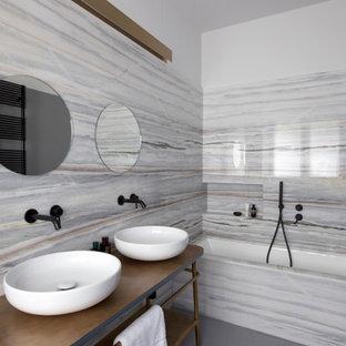 Пример оригинального дизайна: ванная комната в современном стиле с ванной в нише, серой плиткой, белыми стенами, настольной раковиной, столешницей из ламината, серым полом, коричневой столешницей, нишей, тумбой под две раковины и напольной тумбой