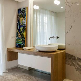 Foto di una stanza da bagno minimal con ante lisce, ante bianche, piastrelle bianche, lastra di pietra, pareti grigie, pavimento in cemento, lavabo a bacinella, top in legno, pavimento grigio e top marrone