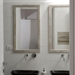 Foto di una stanza da bagno design con piastrelle bianche, lavabo a bacinella e top nero