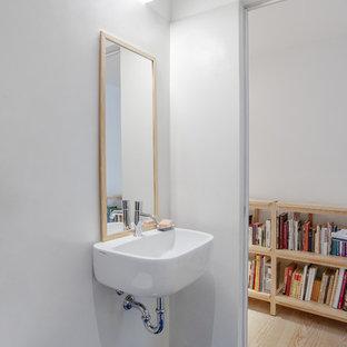 Foto di una stanza da bagno nordica con WC sospeso, pareti bianche, lavabo sospeso e pavimento blu