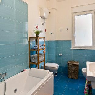 Ispirazione per una stanza da bagno costiera con vasca freestanding, piastrelle blu, piastrelle in ceramica, pareti bianche, pavimento con piastrelle in ceramica e lavabo sospeso
