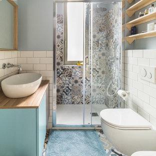 Idee per una stanza da bagno con doccia scandinava con ante lisce, ante blu, doccia alcova, WC sospeso, piastrelle bianche, piastrelle diamantate, pareti blu, lavabo a bacinella, top in legno, pavimento multicolore, porta doccia scorrevole e top marrone
