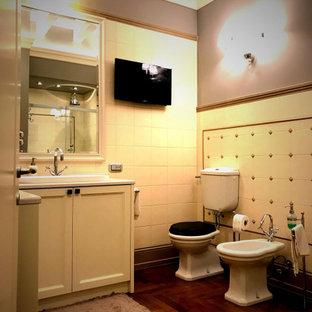 Идея дизайна: ванная комната среднего размера в классическом стиле с фасадами с утопленной филенкой, белыми фасадами, раздельным унитазом, белой плиткой, керамической плиткой, серыми стенами, паркетным полом среднего тона, накладной раковиной, столешницей из известняка, коричневым полом, белой столешницей, напольной тумбой, многоуровневым потолком, угловым душем, душевой кабиной, душем с раздвижными дверями и тумбой под одну раковину