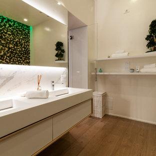 Immagine di una stanza da bagno contemporanea con ante lisce, ante bianche, piastrelle bianche, pareti bianche, pavimento in legno massello medio, lavabo integrato, pavimento marrone e top bianco