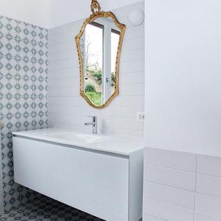 Immagine di una stanza da bagno contemporanea con ante lisce, ante bianche, lavabo da incasso e top bianco