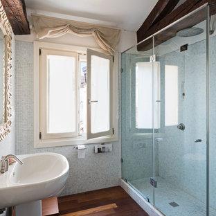 Foto di una piccola stanza da bagno con doccia mediterranea con doccia ad angolo, piastrelle grigie, piastrelle a mosaico, pareti grigie, parquet scuro, lavabo a colonna, pavimento marrone e porta doccia a battente