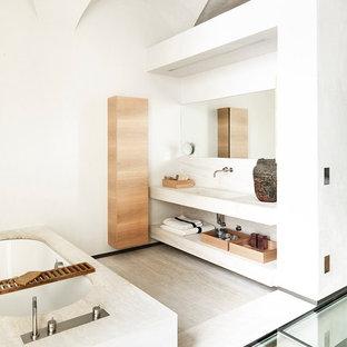 Ispirazione per una stanza da bagno padronale design di medie dimensioni con ante lisce, ante in legno chiaro, vasca da incasso, pareti bianche, pavimento in travertino, lavabo integrato e lastra di pietra