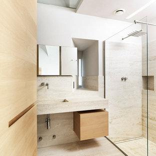Idee per una stanza da bagno con doccia minimal di medie dimensioni con ante lisce, ante in legno chiaro, doccia a filo pavimento, pavimento in travertino, lavabo integrato e lastra di pietra