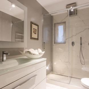 Ispirazione per una stanza da bagno con doccia minimalista di medie dimensioni con ante di vetro, ante bianche, doccia alcova, piastrelle grigie, piastrelle in gres porcellanato, pareti grigie, pavimento in marmo, top in vetro, pavimento bianco, porta doccia scorrevole, WC monopezzo e lavabo integrato