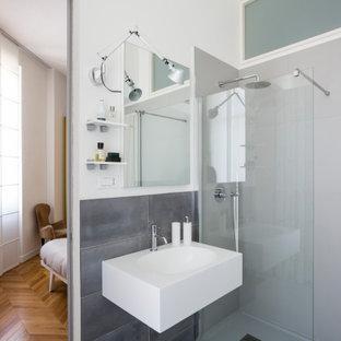 Ispirazione per una stanza da bagno padronale design di medie dimensioni con doccia a filo pavimento, piastrelle grigie, pareti bianche, pavimento in gres porcellanato, lavabo sospeso e pavimento grigio