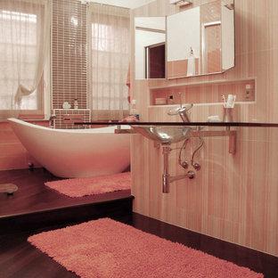 Foto di una stanza da bagno padronale tradizionale di medie dimensioni con pareti arancioni, parquet scuro, top in vetro, ante di vetro, zona vasca/doccia separata, WC a due pezzi, piastrelle multicolore, lavabo integrato e porta doccia scorrevole